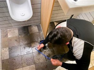Nu-Trend plumbing fixing a blocked sewer drain in a restaurant shopping centre retail store in the bathroom